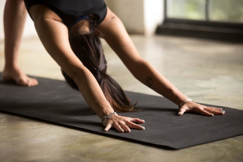 Young attractive woman in downward facing dog pose, studio backg